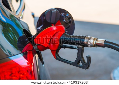 Close up of red fuel nozzle fill enegry of the car.