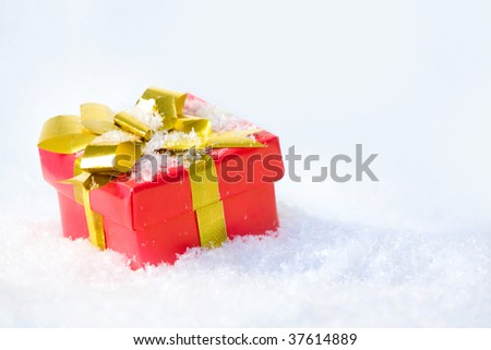 Close-up of red giftbox decorated with bow made up of golden ribbon - stock photo