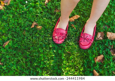 Close up of red moccasins on child's feet - stock photo