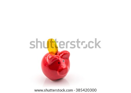 Close up of red piggy bank isolated on white background with golden coin