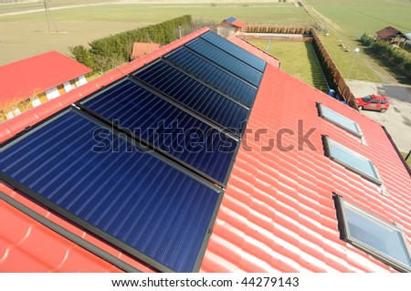 Close up of red roof with solar panels. Green field  in background. - stock photo