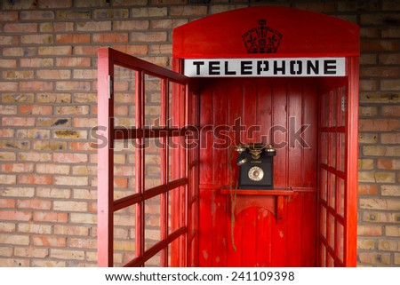 Close Up of Red Telephone Booth with Old Fashioned Telephone and Open Door - stock photo