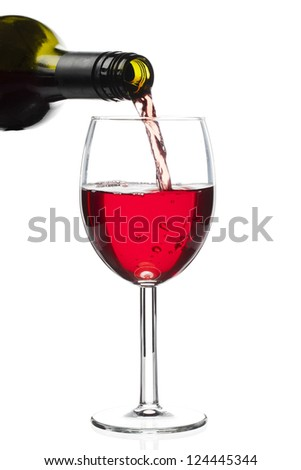 Close-up of red wine pouring down from bottle to glass - stock photo