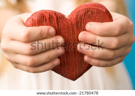 Close-up of red wooden heart in child?s hands showing it - stock photo