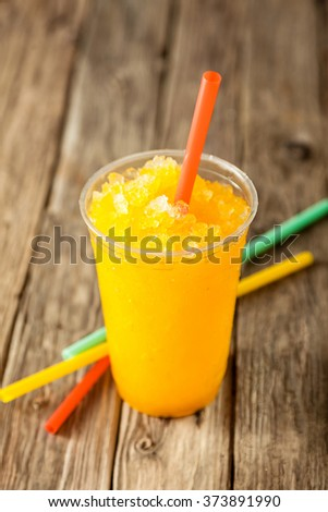 Close Up of Refreshing and Cool Bright Orange Slush Drink in Plastic Cup Served on Rustic Wooden Table with Collection of Colorful Drinking Straws - stock photo