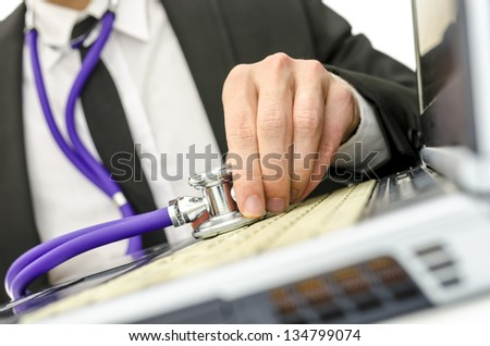 Close up of repairman holding stethoscope on his old laptop keyboard. - stock photo