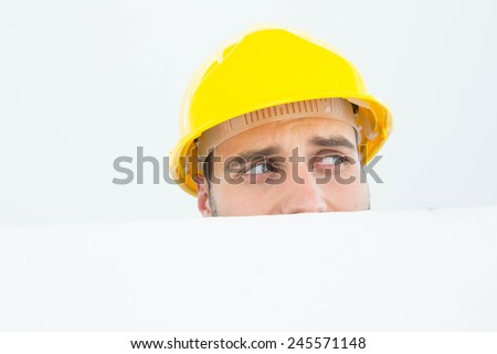 Close-up of repairman wearing hard hat while looking away in front of billboard over white background - stock photo