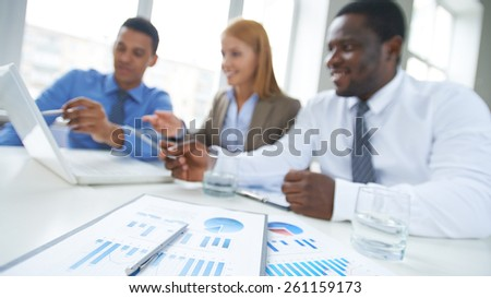 Close-up of reports on table with business people in the background
