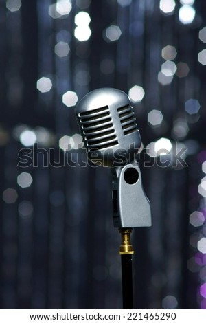 close up  of retro metal microphone or mic against festive bokeh background - stock photo