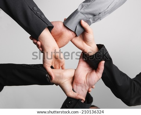 Close up of ring of hands isolated on background. Symbolic, teamwork, cooperation, ties, business team, working together. - stock photo