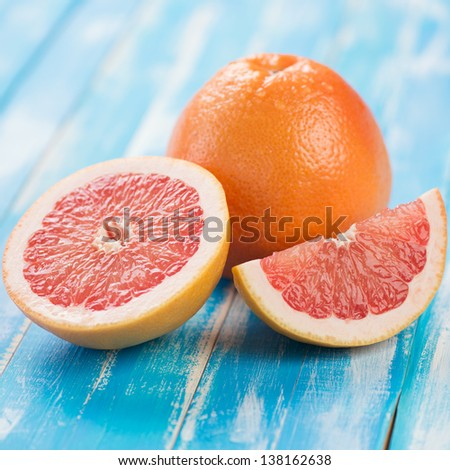 Close-up of ripe grapefruit and its segments on wooden boards - stock photo
