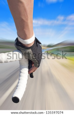 Close up of road bike rider with motion blurred roadway - stock photo
