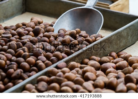 Close-up of roasted chestnut brown crust separating large and small metal tray and scoop on sale in market.