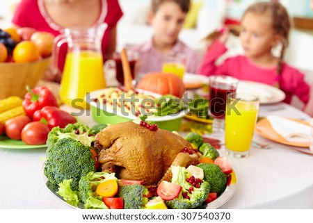 Close-up of roasted chicken on family dining table - stock photo