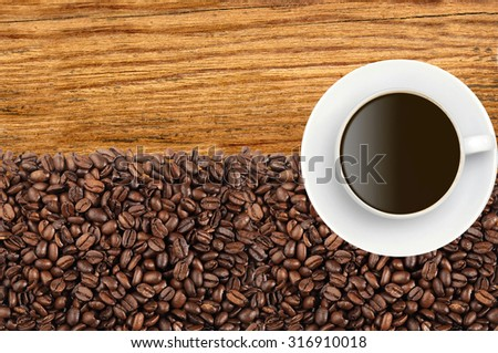 Close-up of roasted coffee beans and coffee cup over wooden background - stock photo