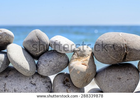 Close Up of Rock Wall Made from Irregular Sized Stones in front of Scenic Ocean Horizon - stock photo