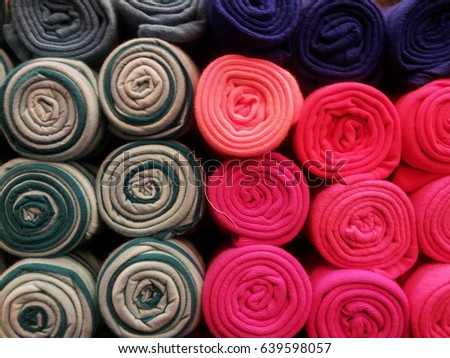 Close up of rolled up material in a market, colored grey and red, Bangkok, Thailand