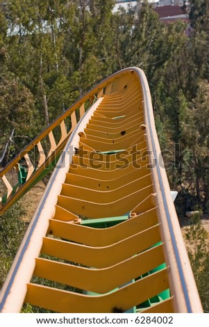 close up of rollercoaster track curving down - stock photo