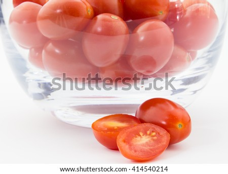 Close up of Roma tomatoes in glass bowl isolated on white  - stock photo