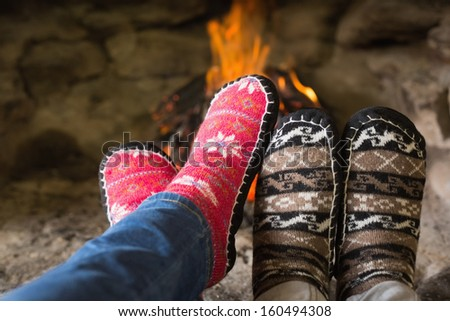 Close-up of romantic couple's legs in socks in front of fireplace at winter season at home - stock photo