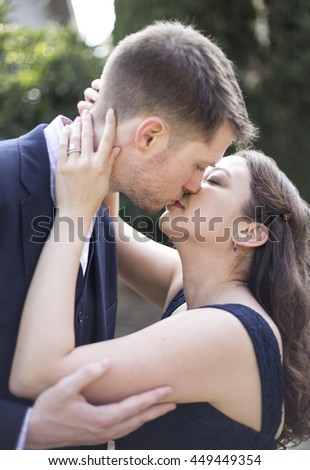 Close up of romantic engaged Caucasian and Asian couple kissing with engagement ring - stock photo