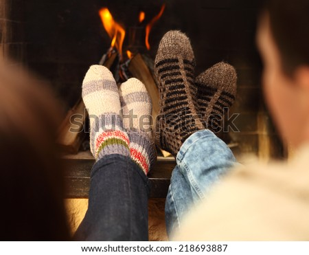 Close up of romantic legs of a couple in socks in front of fireplace at winter season at home
