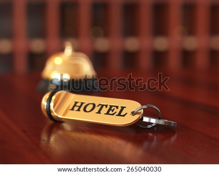 Close up of room access key and bell on wooden reception desk. Soft focus illustration
