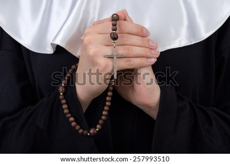 close up of rosary in female nun hands - stock photo