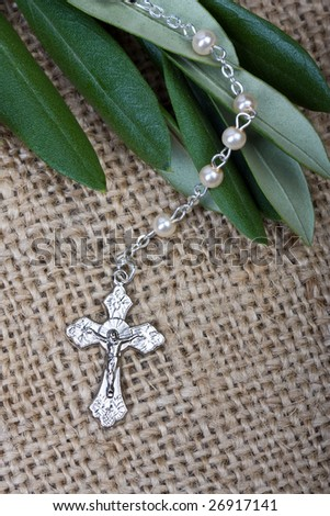 close up of rosary with olive leaves on hessian background