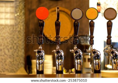 Close Up of Row of Shiny Beer Taps of Different Brews in Bar - stock photo