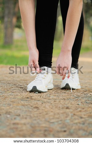 Close-up of runnertie shoelaces on the forest road - stock photo