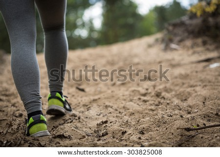 Close-up of running girl's feet on sandy base