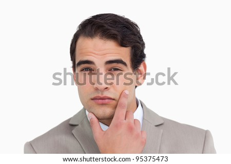 Close up of salesman in thinkers pose against a white background - stock photo