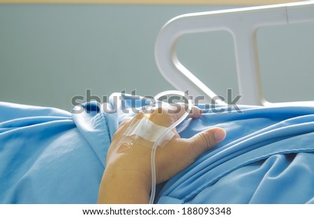 close up of saline solution on hand of man patient in blue clothes lying on the hospital bed - stock photo