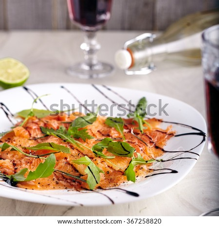 Close up of salmon carpaccio with glass of wine, lime and olive oil bottle on background. Fresh salmon with arugula leaves, lime juice, olive oil, salt and peper. bright photo light wooden background. - stock photo