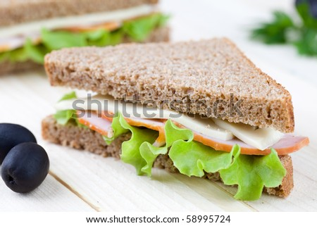 Close up of sandwich on wooden table top - stock photo