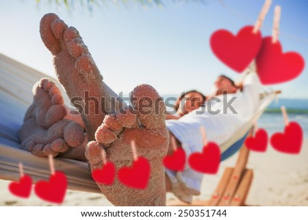 Close up of sandy feet of couple in a hammock against hearts hanging on a line - stock photo