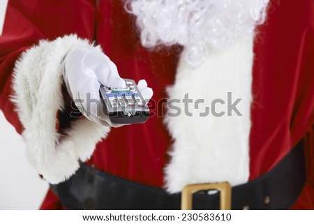 Close Up Of Santa Claus Holding Television Remote Control - stock photo