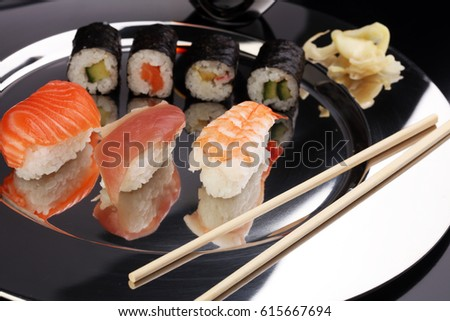 close up of sashimi sushi set with chopsticks and soy - sushi roll with salmon and sushi roll, delicious maki and nigiri