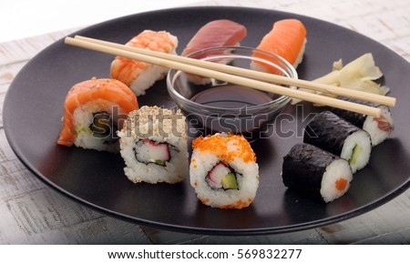 close up of sashimi sushi set with chopsticks and soy - sushi roll with salmon and sushi roll with smoked eel, selective focus.