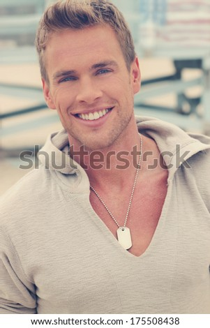 Close up of satisfied smiling handsome young guy looking at camera at home with overall subtle vintage toning - stock photo