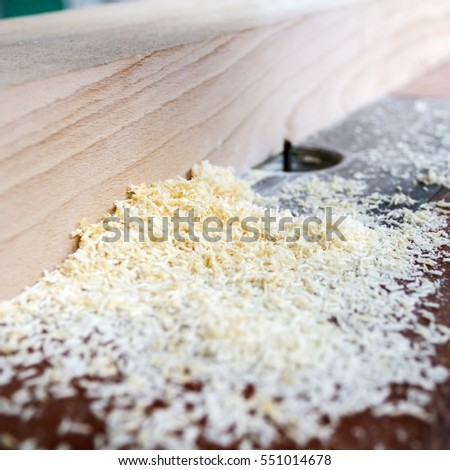 Close-up of sawdust and plank of wood in a carpenters workshop.