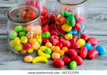 Close-up of scattered colorful candies near glass jars with sweets - stock photo