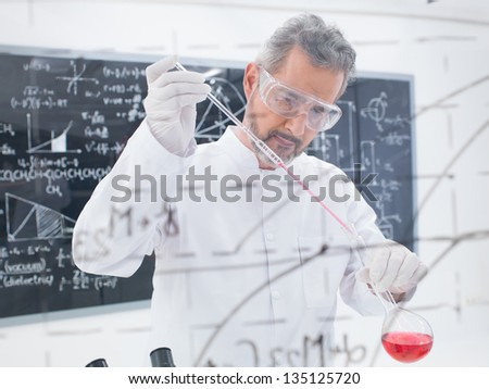 close-up of scientist conducting a chemical laboratory experiment with colorful liquids and a blackboard with formulas on the background - stock photo