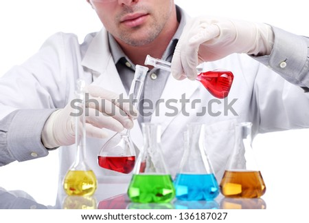 Close up of scientist mixing liquids in flasks in a research lab