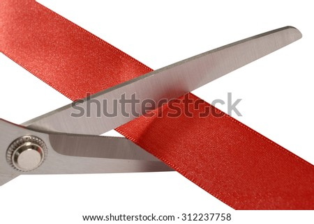 Close up of scissors cutting red ribbon or tape  - stock photo