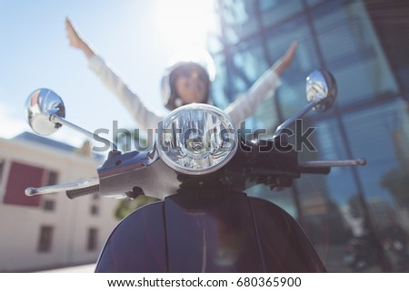 Close up of scooter against businesswoman with arms raised