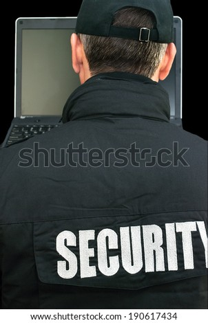 Close-up of security working on a laptop, shot over the shoulder. - stock photo