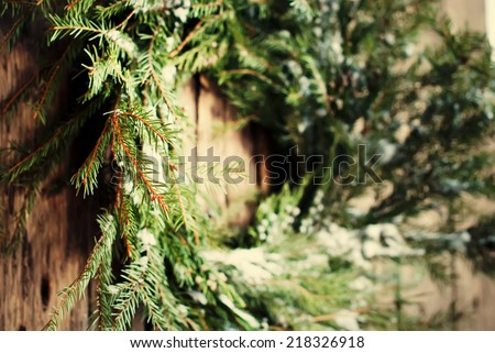 Close up of Selective Focus Natural Wreath with Snow on Wooden Background, warm toned - stock photo