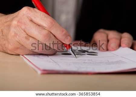 Close up of senior businessman's hand writing notes with red pencil on the desk - stock photo